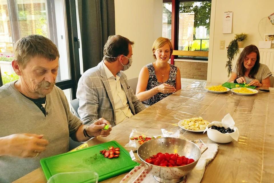 Bewoners Helmut en Carina bereiden het eten voor. Minister Beke, die dinsdag een bezoek bracht, is in gesprek met coördinatrice Marijke Winters.
