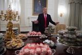 thumbnail: Januari 2019. Omdat de overheidsdiensten gesloten zijn door een politieke impasse in het parlement en er ook geen reguliere catering in het Witte Huis is, serveert Trump een berg fastfood aan footballkampioenen Clemson Tigers, Er zijn honderden hamburgers, o.a. van McDonald's.