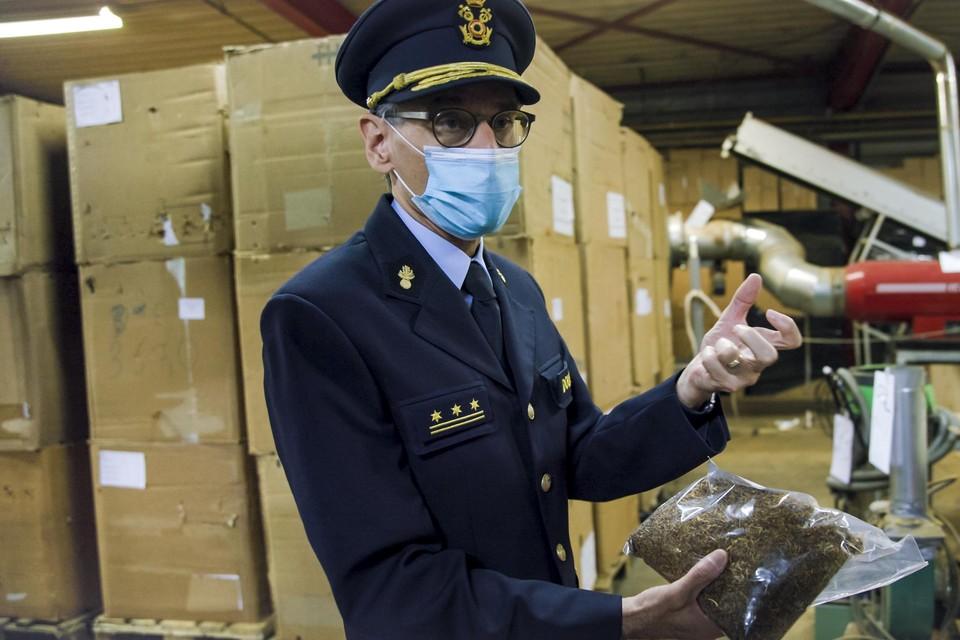 Administrateur-generaal van de douane Kristiaan Vanderwaeren toont  een pakket met versneden tabak in de illegale fabriek in Tongeren.