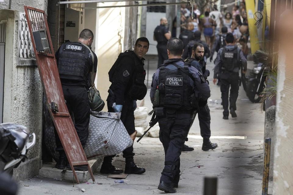 Politieagenten dragen een slachtoffer in een laken een huis uit, tijdens hun inval in een favela van Rio de Janeiro.
