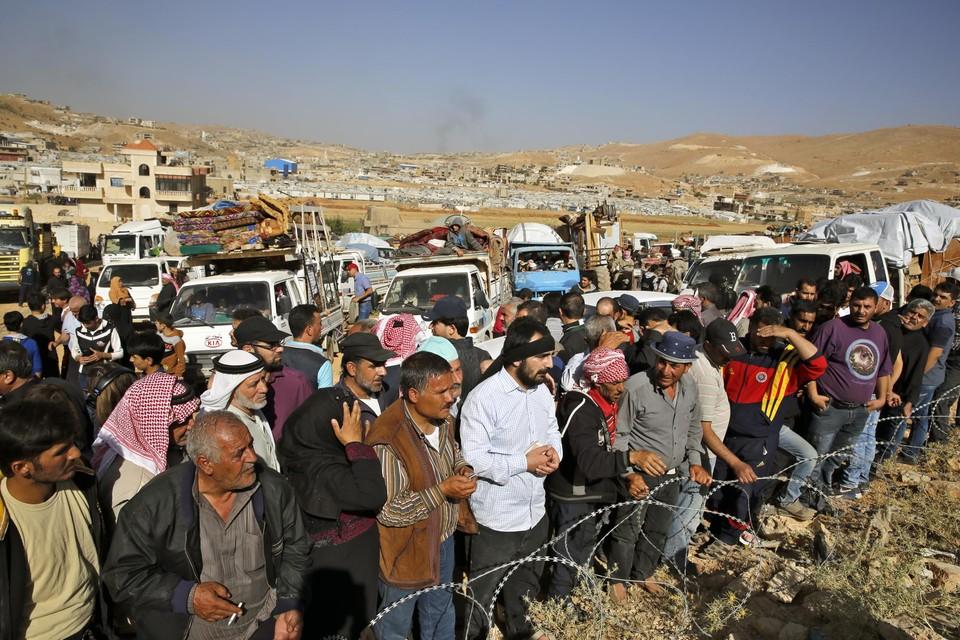 Archiefbeeld: Syrische vluchtelingen wachten net over de grens met Libanon om hun land opnieuw binnen te komen.