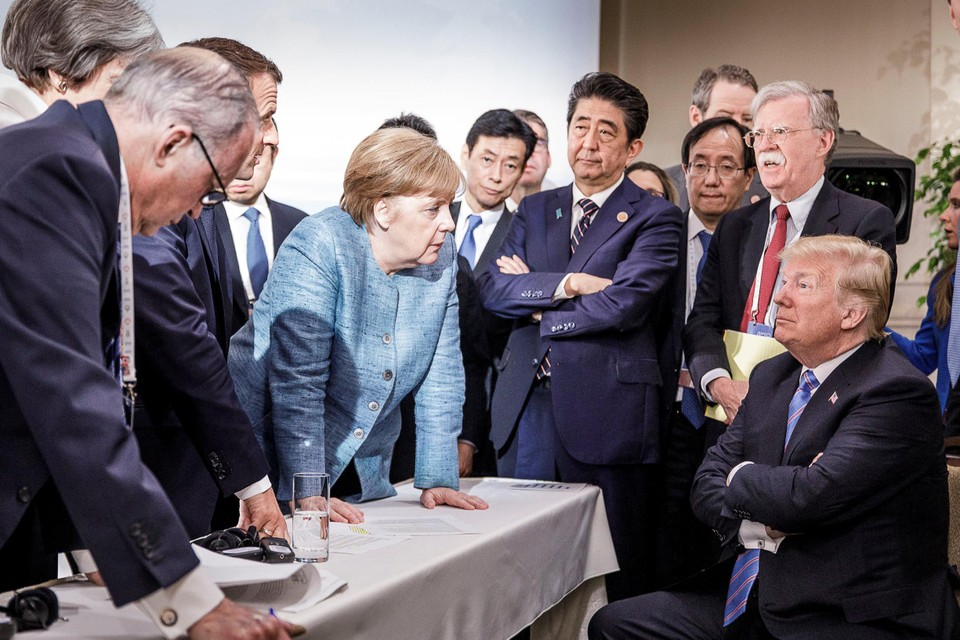 Juni 2018. Op de G7-top in Quebec heerst een raar sfeertje tussen de wereldleiders. Trump zit als enige neer, defensief de armen gekruist, terwijl Macron en Merkel een punt proberen te maken.