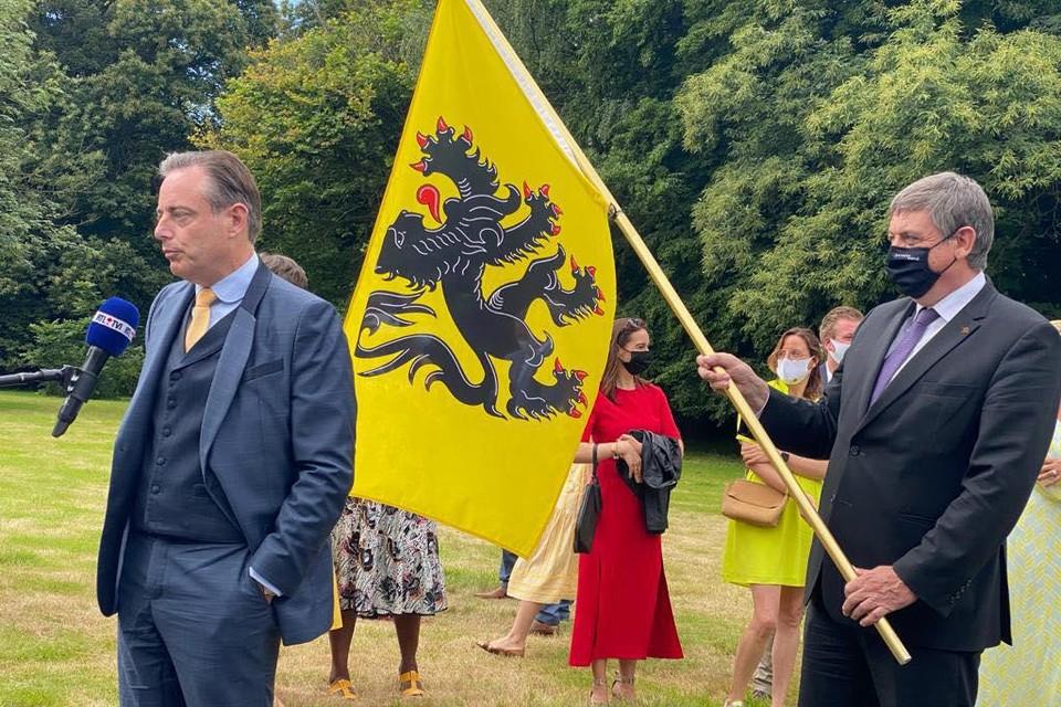 """De Wever tijdens een interview met RTL-TVI, met achter hem Jan Jambon. """"Als je op 11 juli de Franstalige media te woord staat, is een schildknaap met de vlag essentieel"""", postte De Wever op Facebook."""