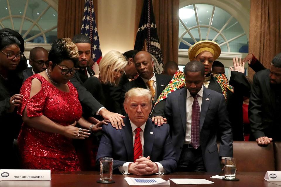 Februari 2020. Met een grote religieuze achterban moet Trump ook dat aspect in beeld laten komen. Hier bidt de president (enkel hij heeft de ogen open) samen met vertegenwoordigers van de Afro-Amerikaanse gemeenschap.
