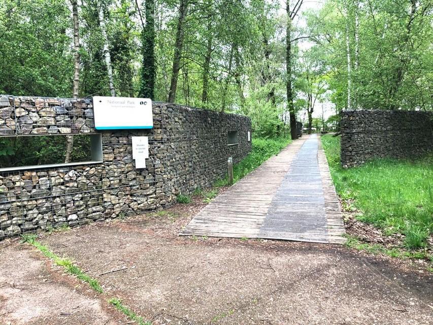 Ondanks de waarschuwing van de gouverneur lopen meerdere wandelaars ongestoord in en uit de toegangspoort Nationaal Park Hoge Kempen bij Domein Pietersheim in Lanaken.