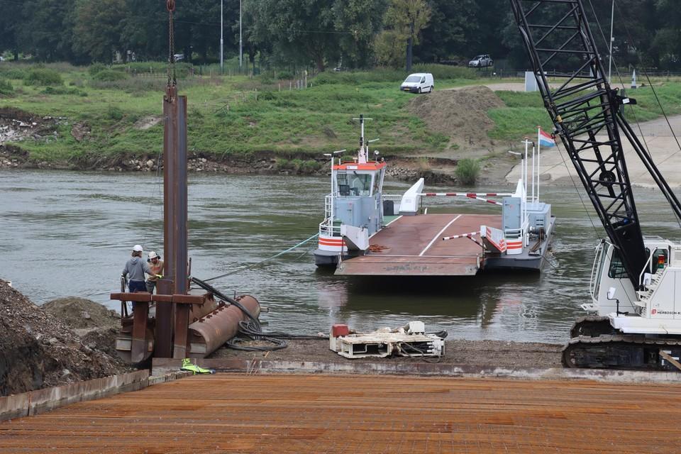 Stalen damplanken van 9 meter lang worden in de Maas geheid op het einde van een nieuwe straat die reeds voorzien is van vlechtwerk uit ijzer.