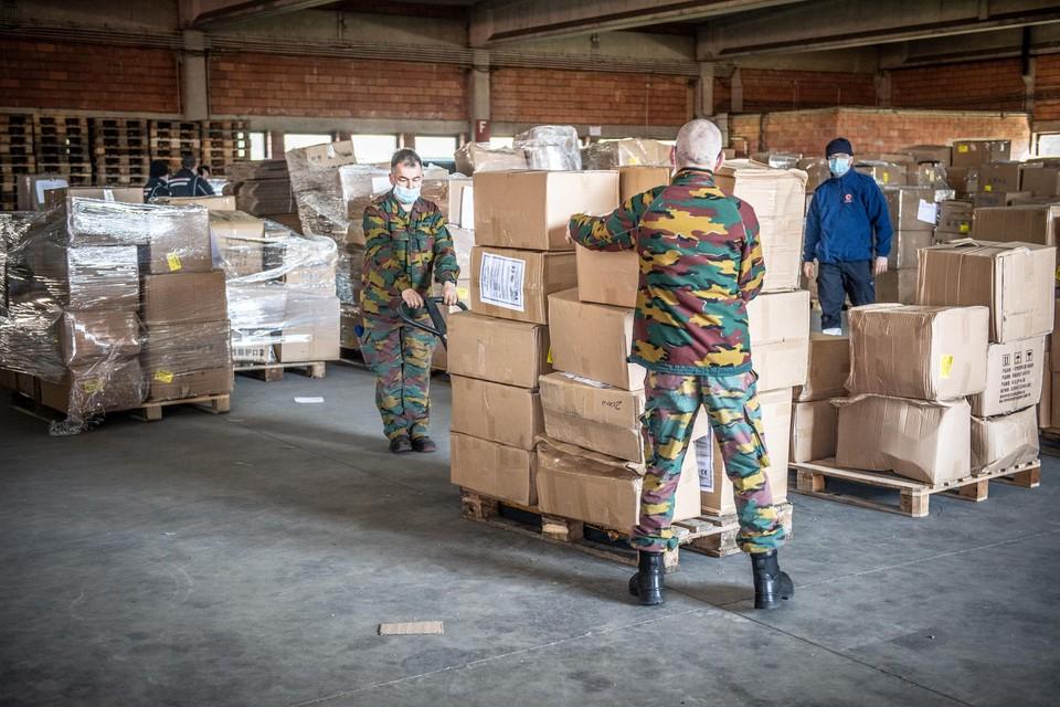 Militairen in de kazerne van Peutie verzetten de dozen met de bestelde mondmaskers.
