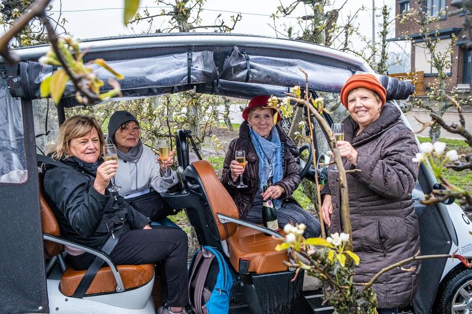 Lea (70), Huguette (72), Mart (72) en Sonja (69) genieten van bubbels tussen de natte bloesems.