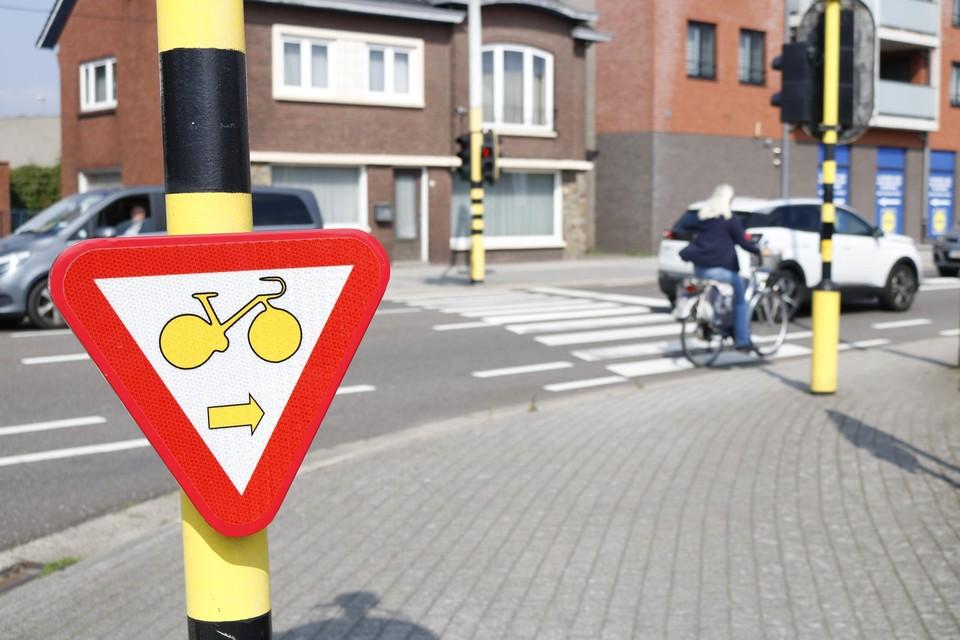 Borden met een omgekeerde driehoek met daarin een gele fietser en een pijl naar rechts, geven die nieuwe regeling aan.