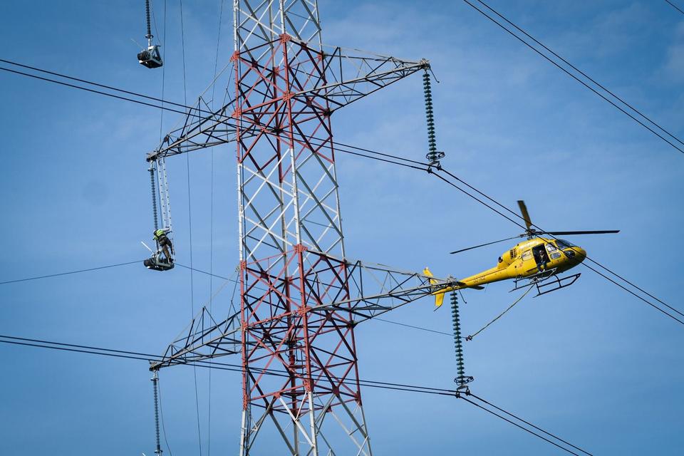 De man op het laddertje hoog in de mast legt de trekkoord over de wieltjes terwijl zijn collega in de helikopter nauwgezet toekijkt.