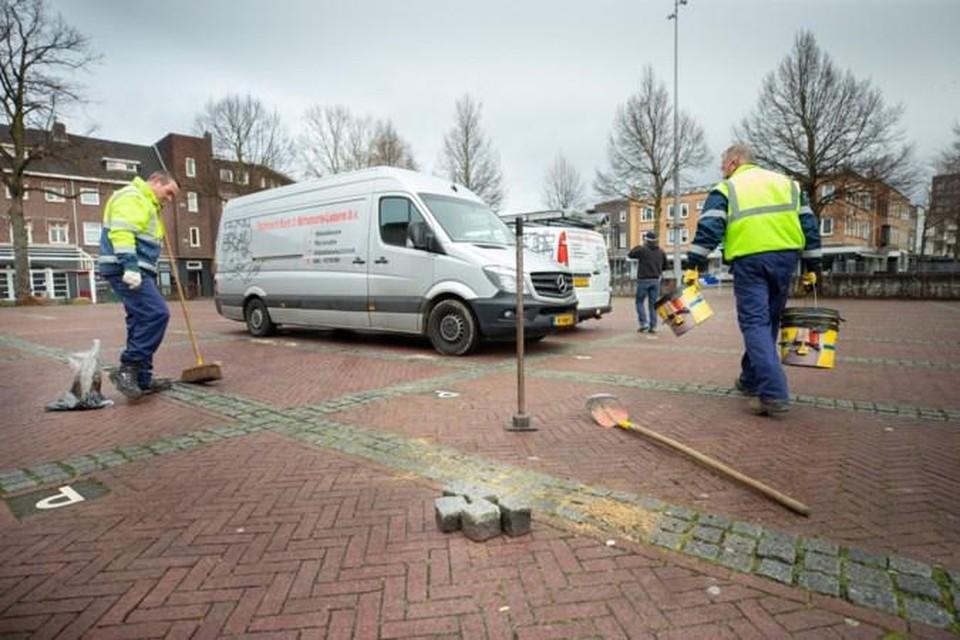 Stratenmakers herstellen de schade op de parkeerplaats voor het gemeentehuis.