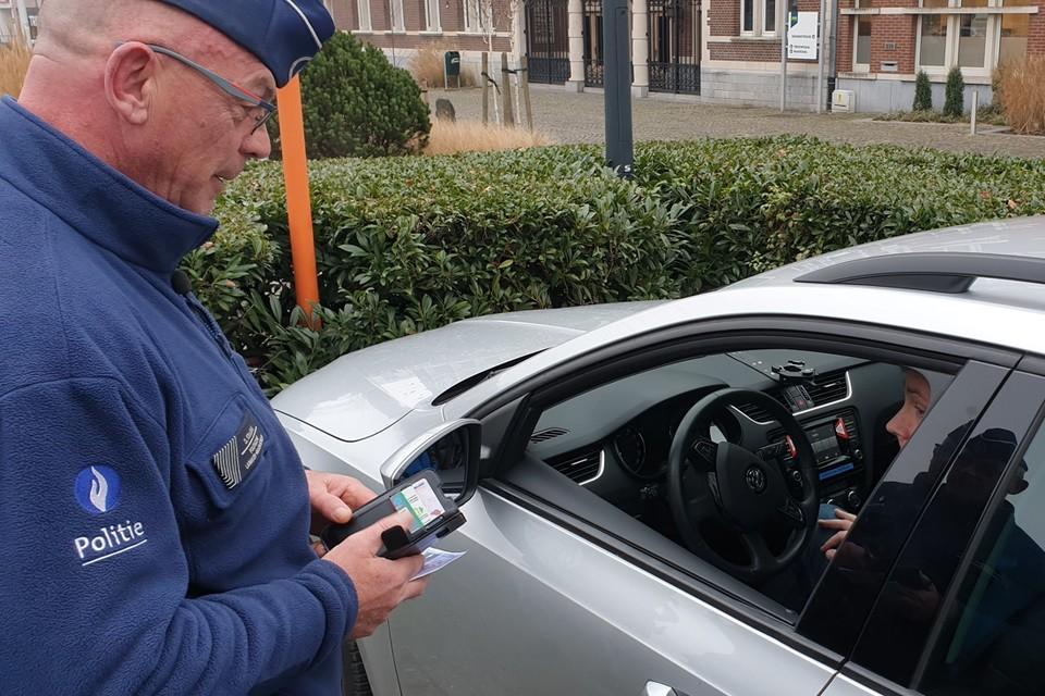 Een agent toont hoe hij een bestuurder snel controleert met de nieuwe politieapp.