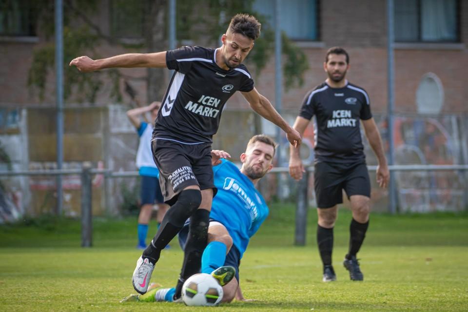Dieter Bussels probeert met een tackle Umut Asan van de bal te zetten.