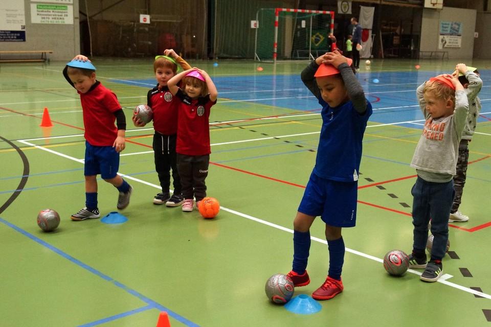 Kleuters van drie tot vijf jaar leren hun eerste voetbalstapjes op een speelse manier zetten in de sporthal.