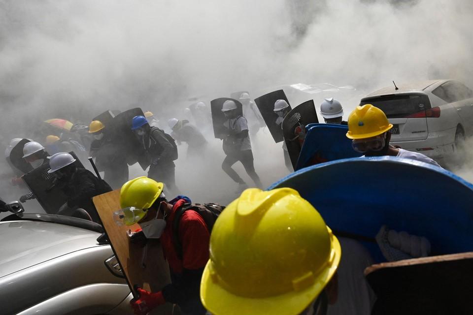 Demonstranten met zelfgemaakte schilden trotseren traangas in de straten van Yangon.