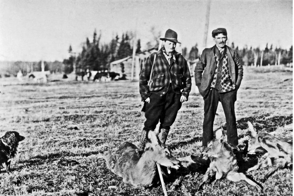Met een pijp en een herenbroek poseert Annette (links) naast een Canadese jager. Jagen deed ze eerst op bevers, al waren grijze beren eigenlijk het doelwit.