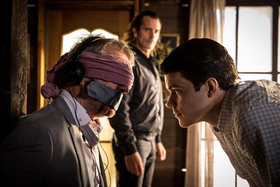 Phil Frisco (Lucas Van den Eynde) wordt ontvoerd door twee 'aparte' criminelen (Koen De Bouw en Vincent Van Sande).