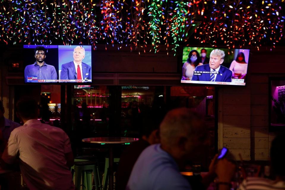 Tv's in een bar tonen beide uitzendingen: links met Biden, rechts met Trump.