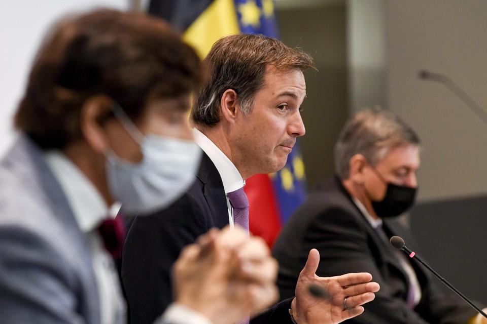 Alexander De Croo legt de beslissingen van een vorig Overlegcomité uit. Elio Di Rupo en Jan Jambon luisteren.