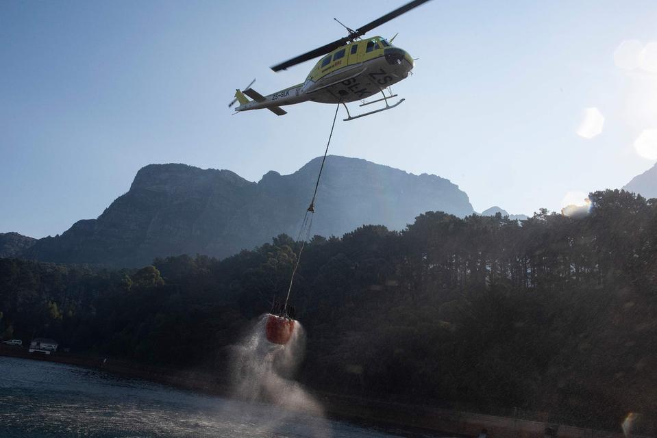 Onder meer met blushelikopters wordt geprobeerd het vuur te doven.