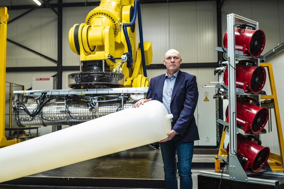 """Johan Potargent met een waterstoftank en met de robot op de achtergrond. """"Waterstof wordt een gigantische markt."""""""
