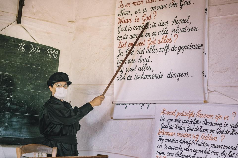 Ook in 1919 moest de onderwijzeres met een mondmasker op in het klaslokaaltje staan. Zo voel je in Bokrijk hoe het dorpsleven verstoord werd door de Spaanse griep.